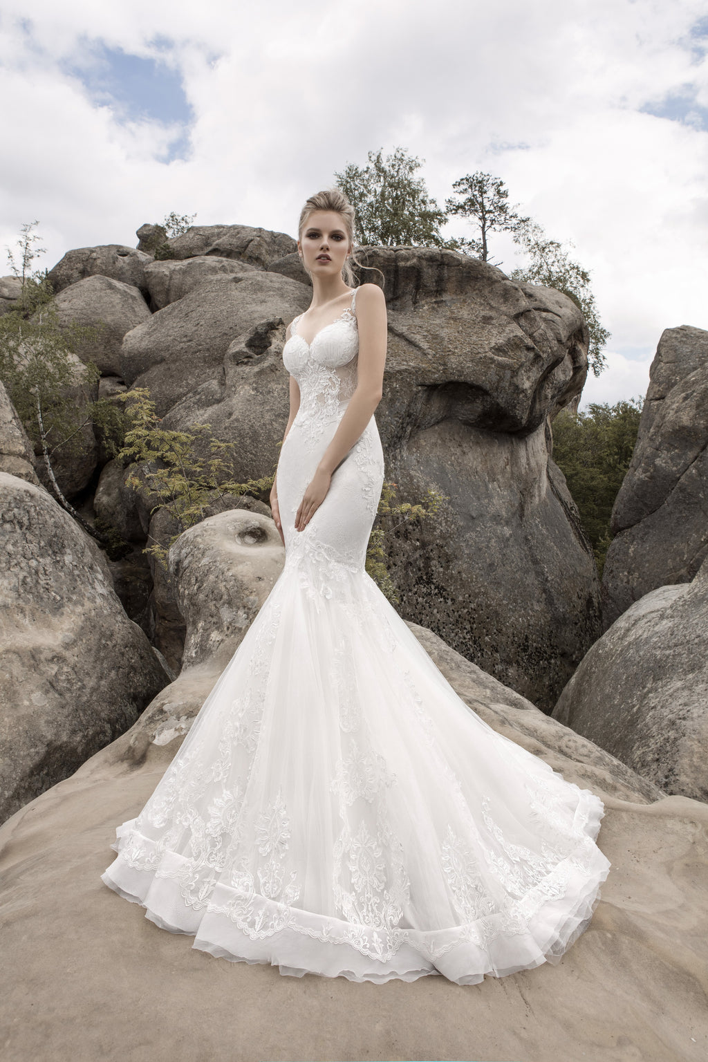 This unique mermaid gown has a sheer lace bodice and features an illusion lace back.
