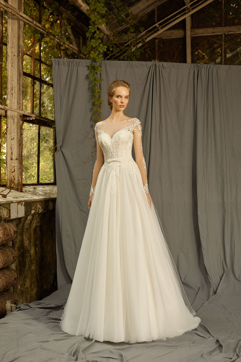 This classical A-line dress features a sweetheart bodice with illusion neckline, beautiful lace décor, and sheer long sleeves.