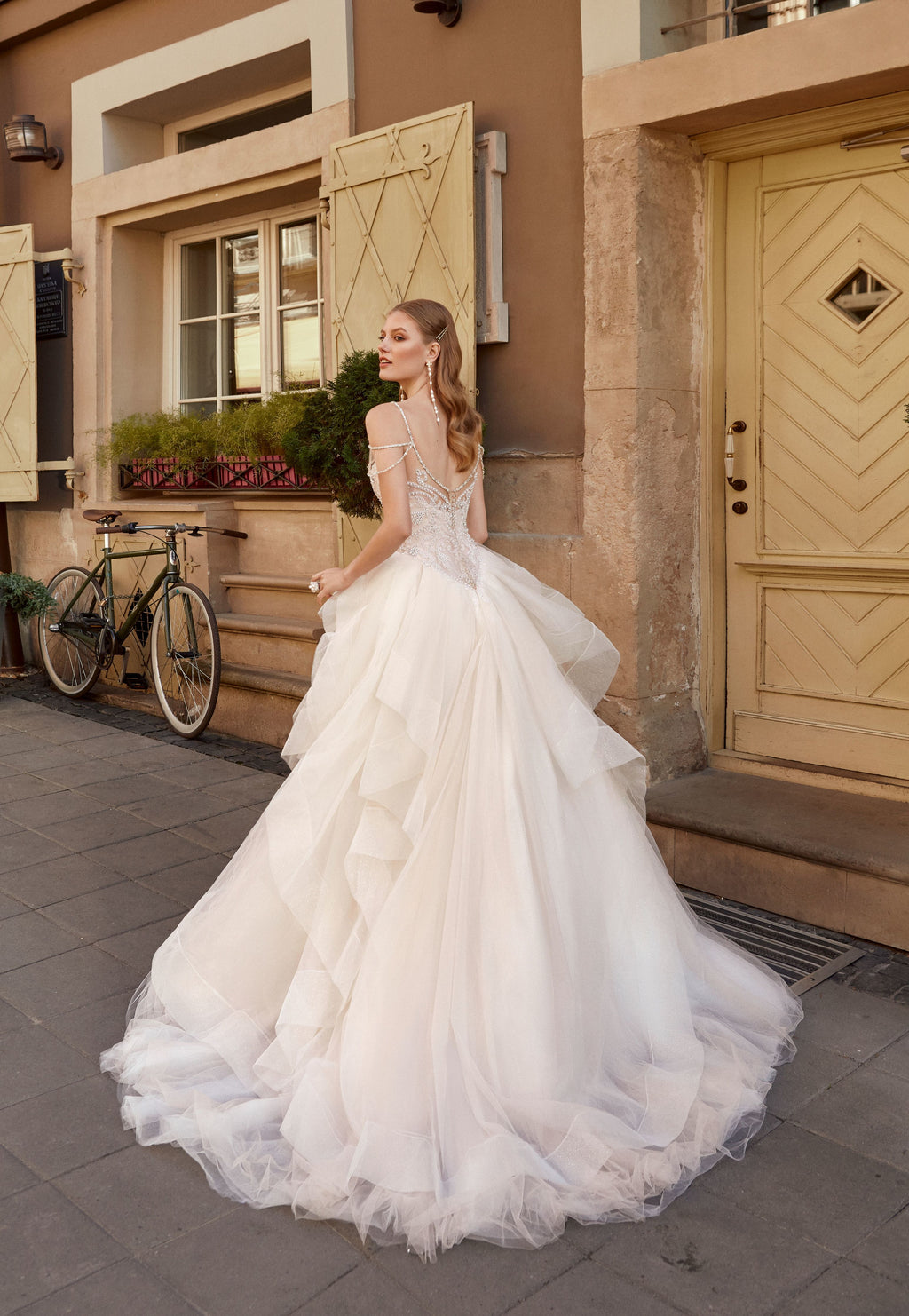 This princess ball gown has a bodice embroidered with pearls, beads and crystals, with strands of pearls and crystals falling over the shoulders and neckline. Its skirt features tulle frills with sparkling edges.