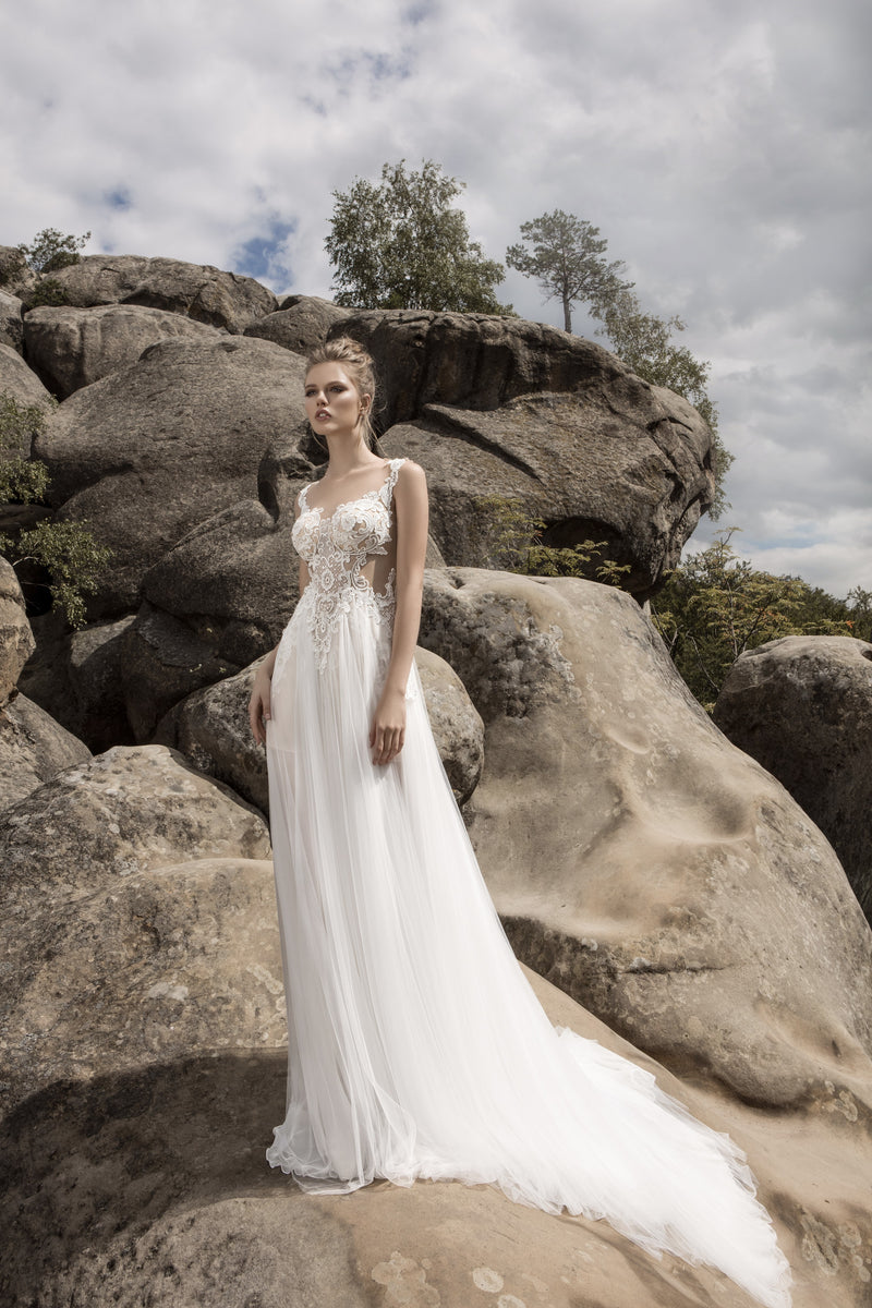 This wedding dress is ideal for any bride dreaming of a romantic beach wedding. Featuring corded lace on its sheer fitted bodice, and breathtaking lace illusion back, it is truly a unique seaside statement. The long chiffon layer over the short skirt runs into a beautiful train.