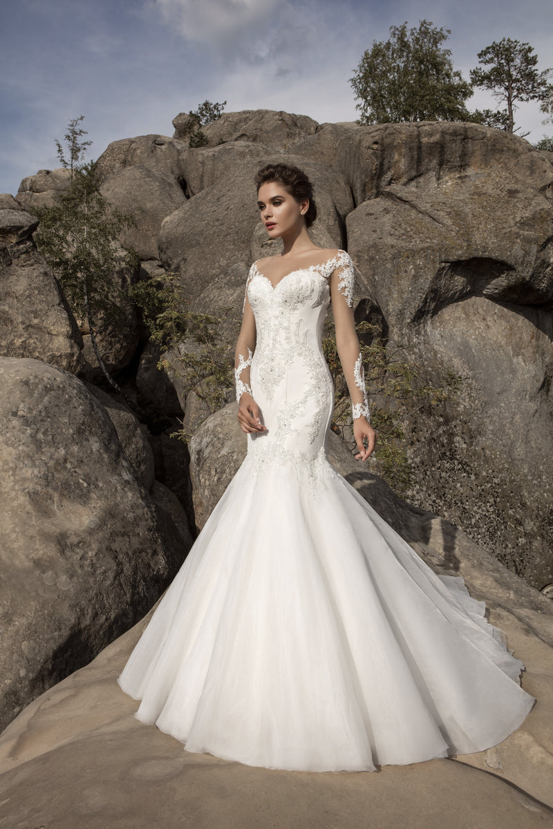 This figure flattering mermaid wedding dress is decorated with lace appliques. The stunning dress features a sweetheart neckline, an illusion back with fabric covered buttons, and alluring illusion lace sleeves.