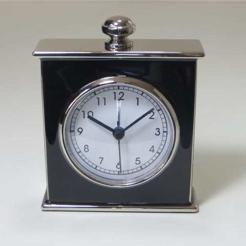 Small square black enamel and silver metal alarm clock.