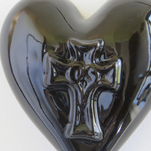 Close up of black glossy ceramic heart with embossed cross.