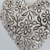 Close up of matt cream daisy ceramic heart.