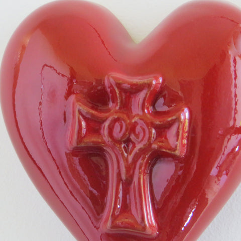Close up of ceramic red glossy heart with embossed cross.