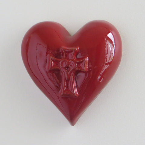 Ceramic red glossy heart with embossed cross.