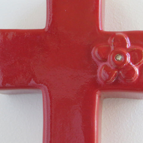 Close up of gloss red ceramic cross with daisy and diamante.