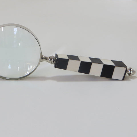 Large magnifying glass with square black and white checked bone handle - side on view.