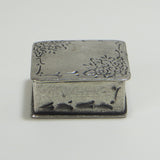Small square solid pewter trinket box with flower design on lid.