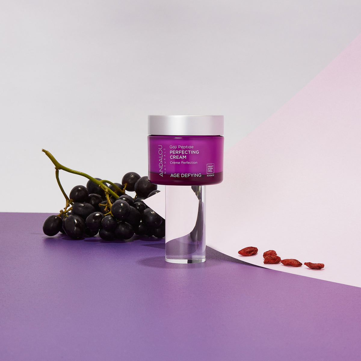 Andalou Naturals Age Defying Goji Peptide Perfecting Cream jar and concord grapes