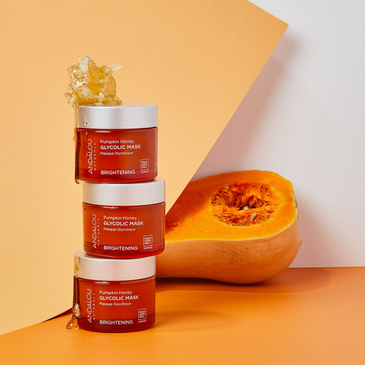 tower of Andalou Naturals Brightening Pumpkin Honey Glycolic Mask jars with honeycomb and half of a butternut squash