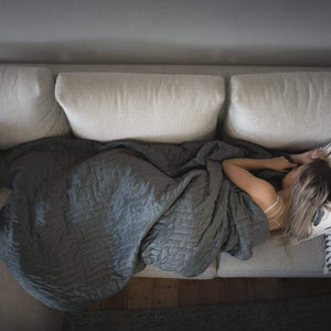 Bird view of a blond young woman lying on a couch, covered with Calming Blanket's weighted blanket.