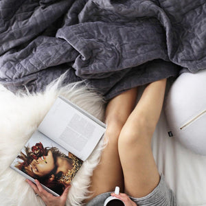 girl on bed wrapped in blanket drinking tea and reading a magazine