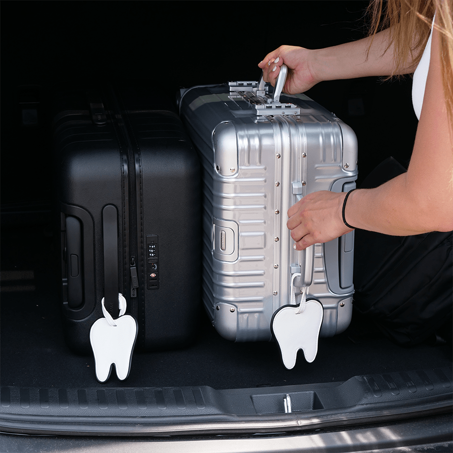 two suitcases in back of car with tooth-shaped luggage tags