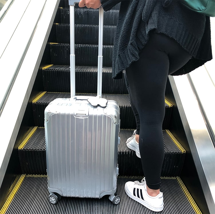 Woman on escalator with silver suitcase and tooth tag