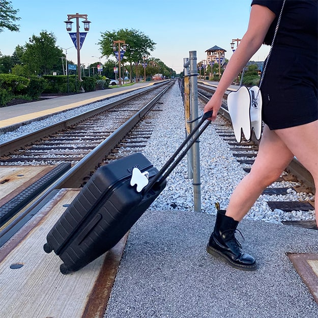 women crossing train tracks with suit case and tooth purse