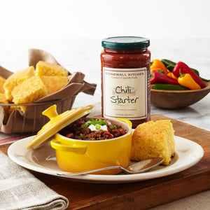 chili in a yellow crock with cornbread in a basket and a jar of Stonewall Kitchen Chili Starter