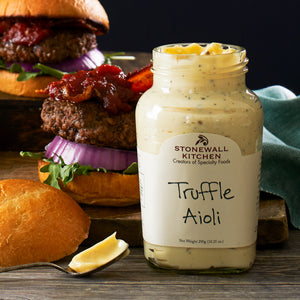 jar of Stonewall Kitchen Truffle Aioli in front of hamburgers with bacon, lettuce, and red onion