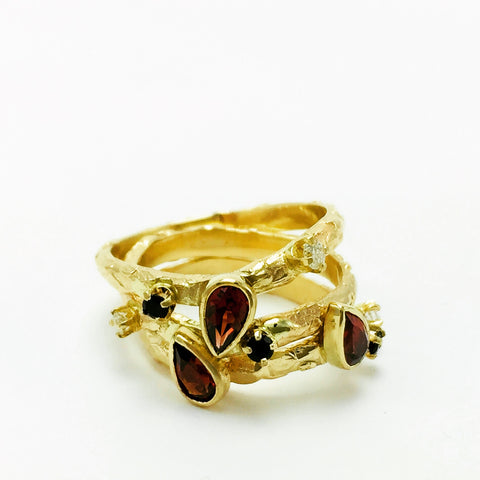 Trio of gold rings, with Diamond, Onyx, and Garnets