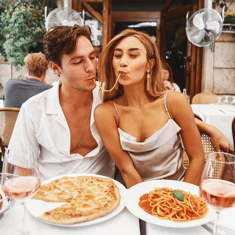Couple eating spaghettis in a restaurant located in Rome, one of the best vacation spots for couples
