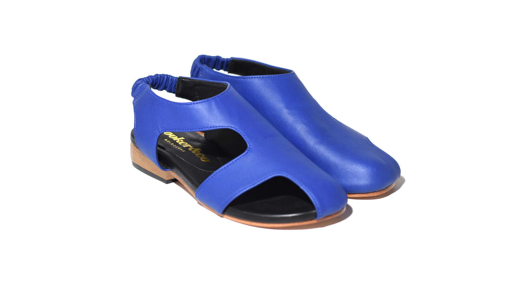 side view of Asymmetric bright blue leather sandal, covered toe, stacked leather heel