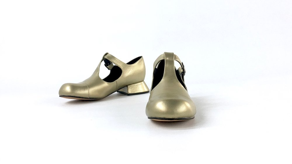 front view of matt metallic gold leather mary jane or t bar style shoe