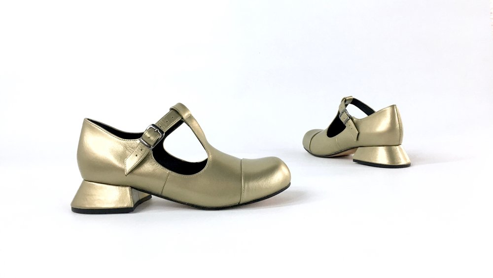 side view of matt metallic gold leather mary jane or t bar style shoe