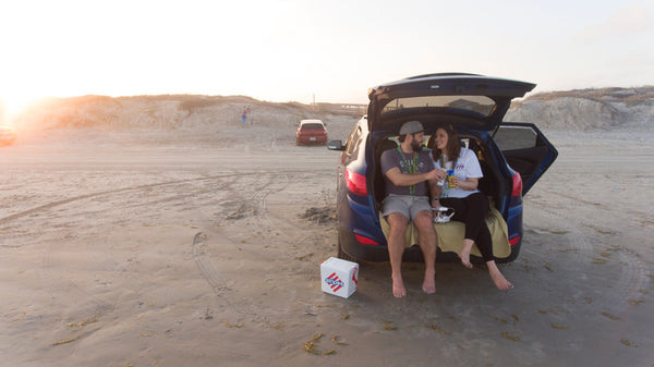 couple hanging out in back of car with trunk door open on beach - quality time