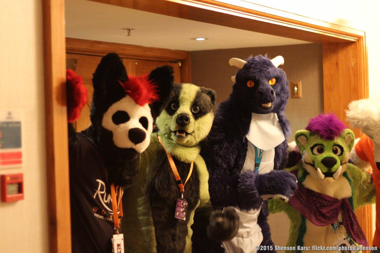 photo of some of my suits at confuzzled 2015, a dog with skull pattern on its face pre made suit by me, an unknown green badger fursuiter, a blue dragon (bloo), and an orkish otter (Pa-daka) stand together next to hotel double doors. photo by shenson Karu