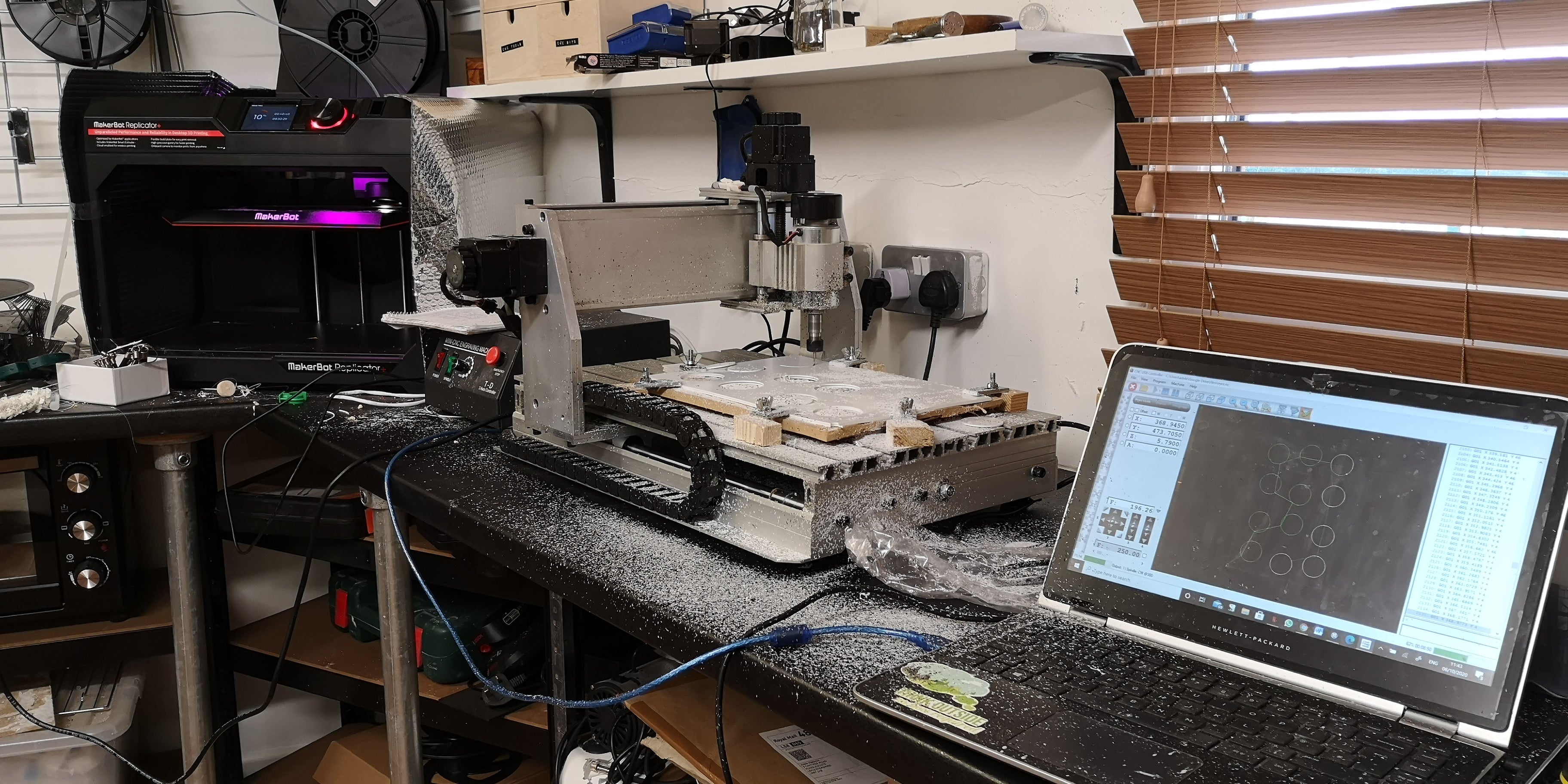 photo of my machine set up, a 3D printer and a CNC milling machine sit on a counter next to a laptop. the counter top is dirty with bits from the milling machine that has just been used