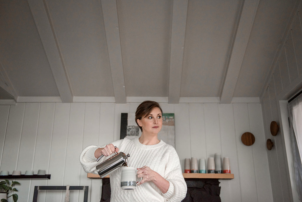 Me pouring coffee into my grey mug inside a white cottage with vases on the mantle in the background.