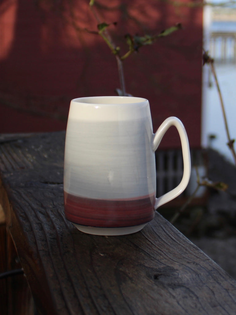 Red Sea mug with red siding backdrop.