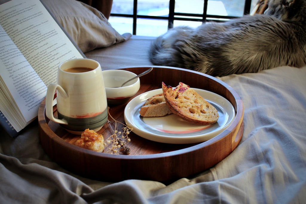 Breakfast tray and book in bed with grey cat looking out the window.