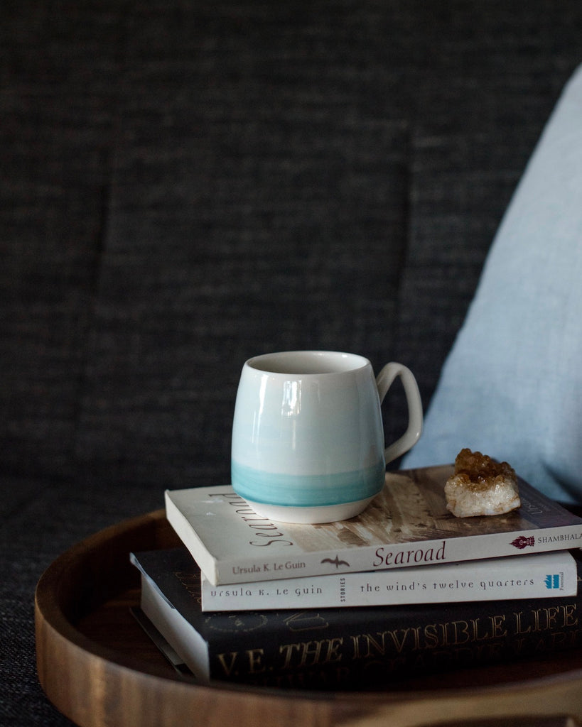 Small teal mug on a stack of books next to a crystal.