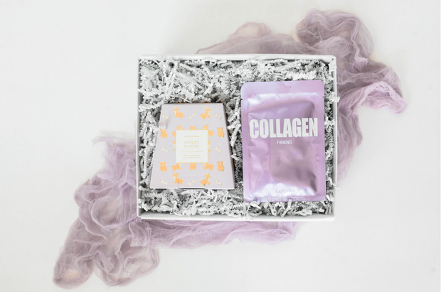 The Violet gift set is the mini perfect gift for her or relaxation gift that includes a violet and rose scented candle with a puppy and bone gold leaf print and a firming collagen face mask, perfect for an at home spa day.