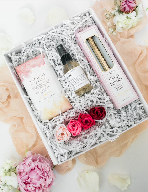 The Magnolia gift set is the perfect bridal shower gift for any bride-to-be. This bridal inspired set includes the one and only Bling Brush, a natural on the go jewelry cleaner to ensure her bling sparkles just as bright as she does on her big day, a moisturizing rose petal hydration mist, a magnolia scented bath fizz bar, and a pink ombre set of beautiful rose petal shaped soaps.