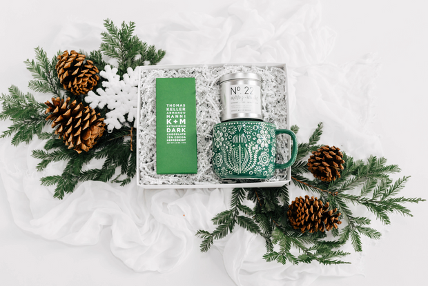 "The Peppermint is exactly what Santa ordered.  This gift box includes a silver ""merry & bright"" tin candle with scents of bayberry, clove, nutmeg and cedar, a large rustic green and white mug with a Scandinavian-inspired embossed pattern, perfect for sipping hot chocolate, and a delicious peppermint dark chocolate bar created by famous chef, Thomas Keller."