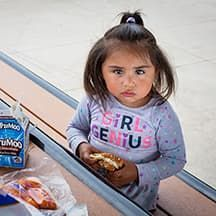 Little girl eating. Hunger and poverty