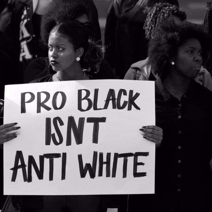 "Women holding a sign that says ""Pro Black Isn't Anti White"
