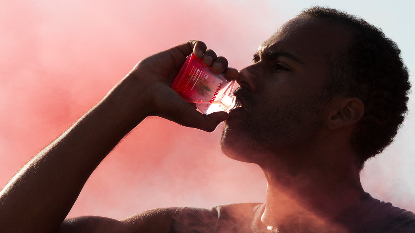 African American athlete drinking HVMN Ketone with red smoke in background
