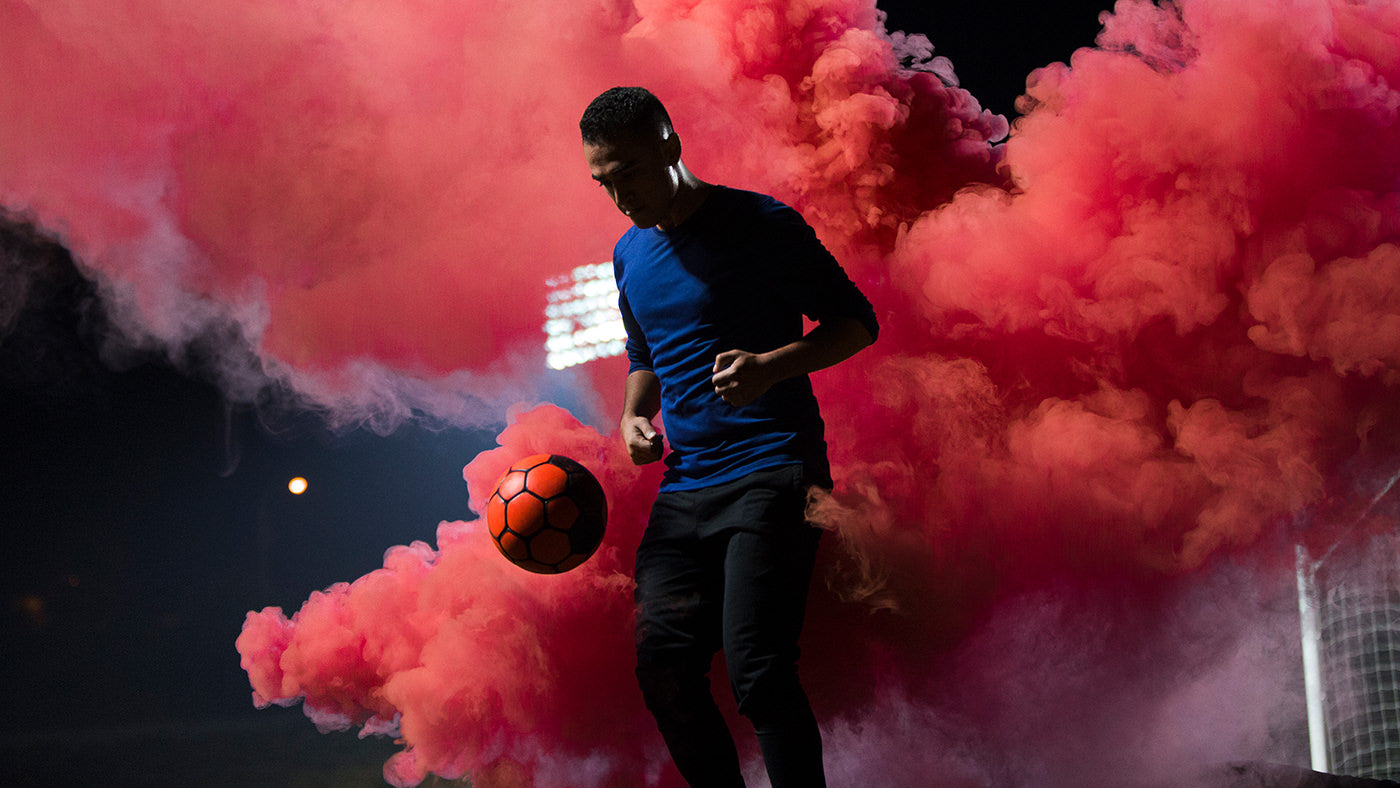 Soccer player juggling with red smoke in background