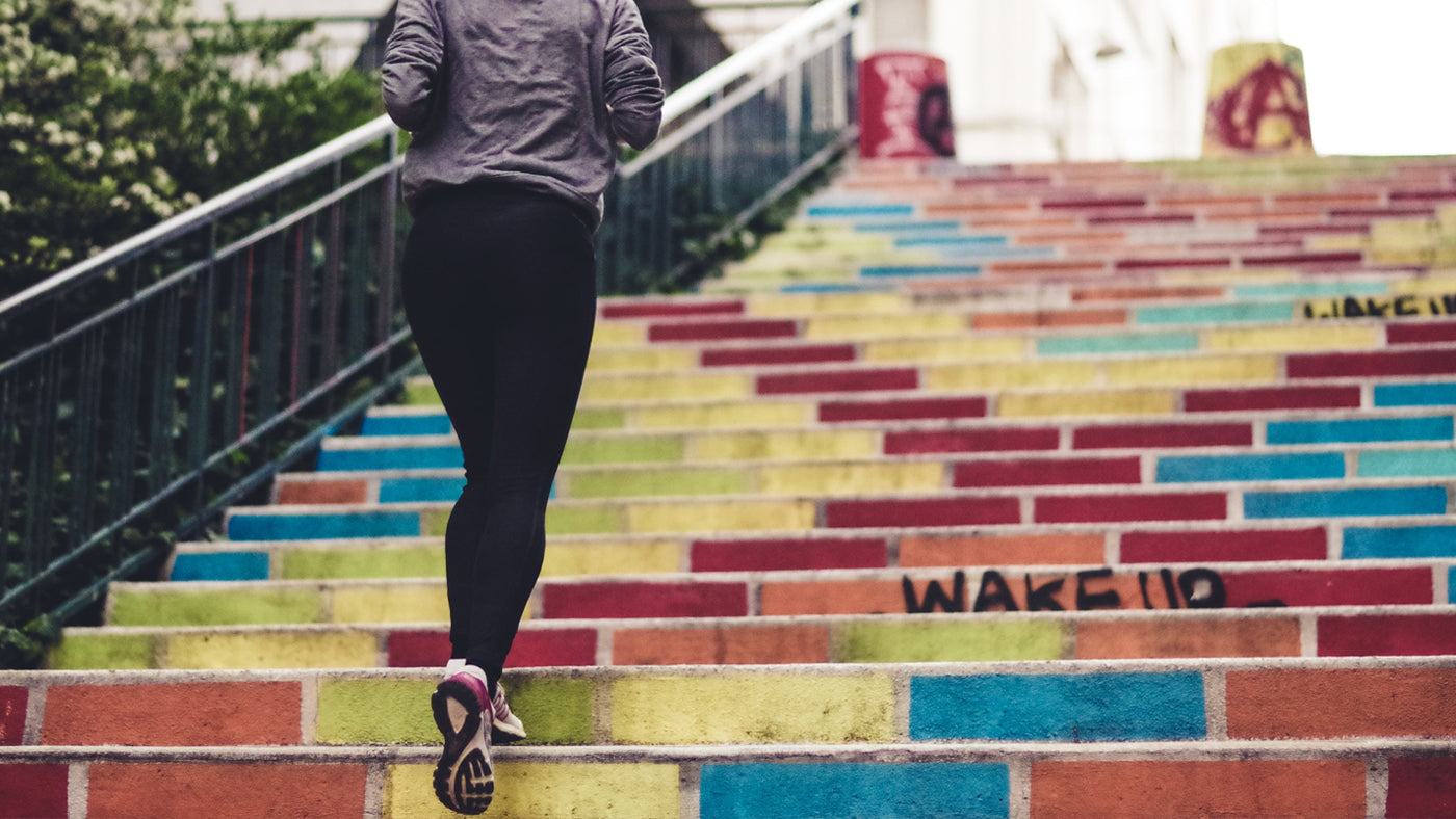 A female runner jugging up colorful stairs