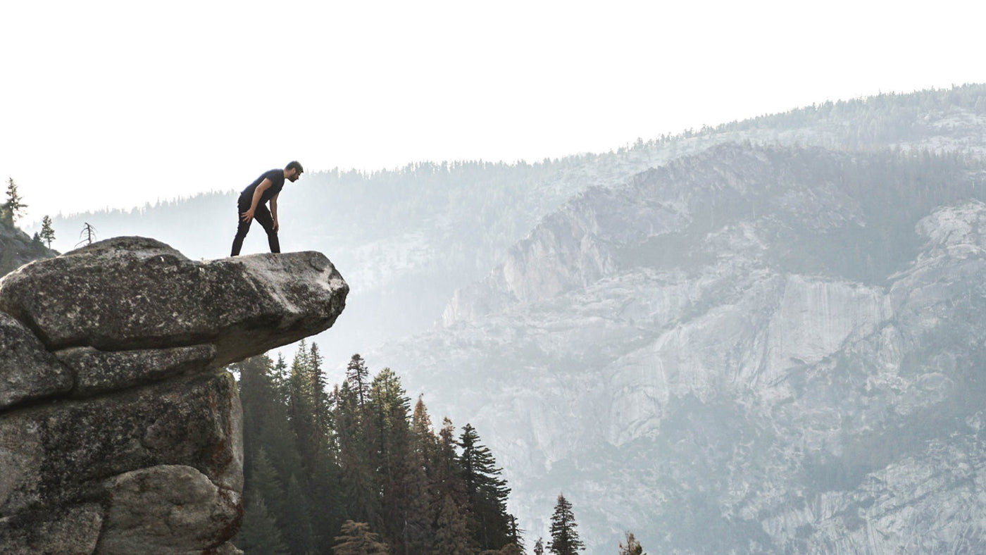 A runner looking over the edge of a cliff
