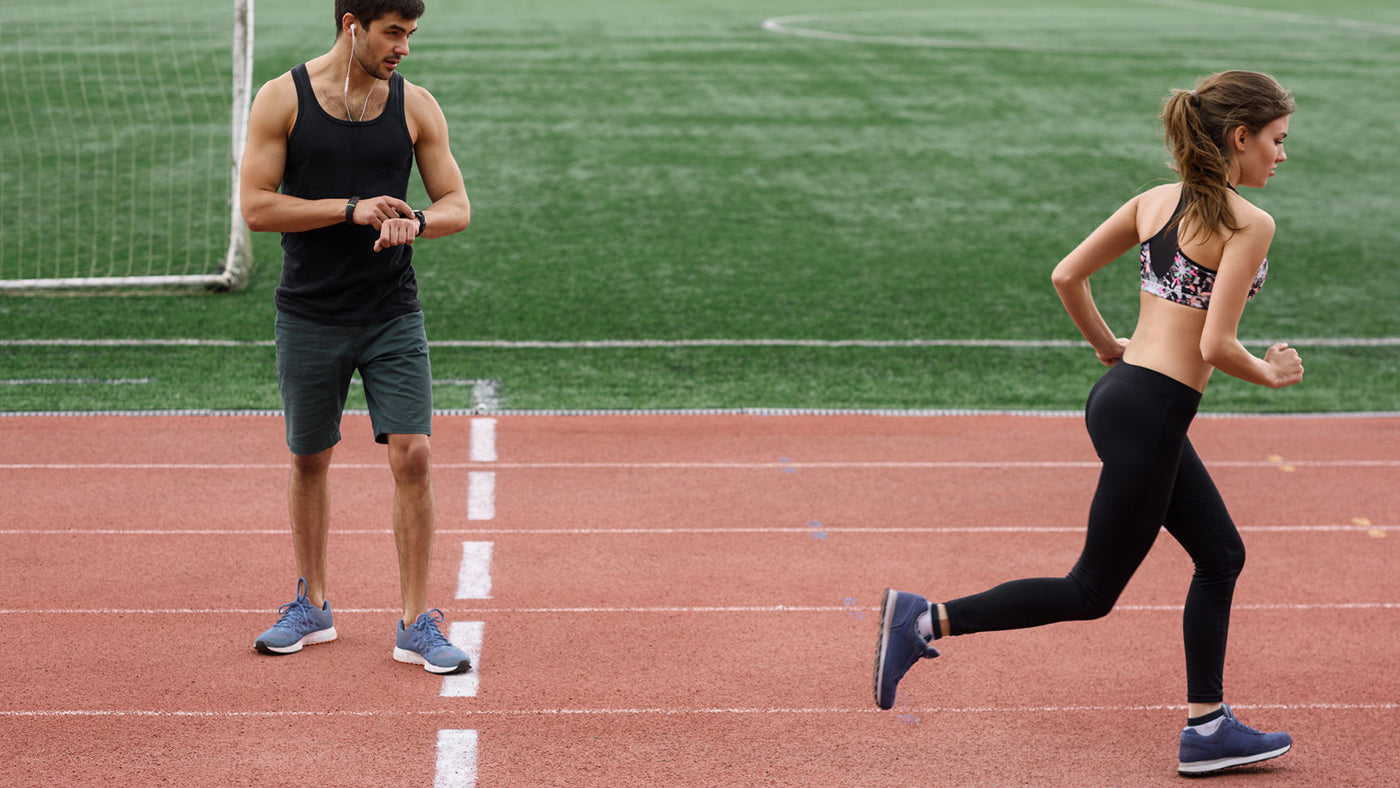 A female runner and male coach figuring out lactate threshold on a track
