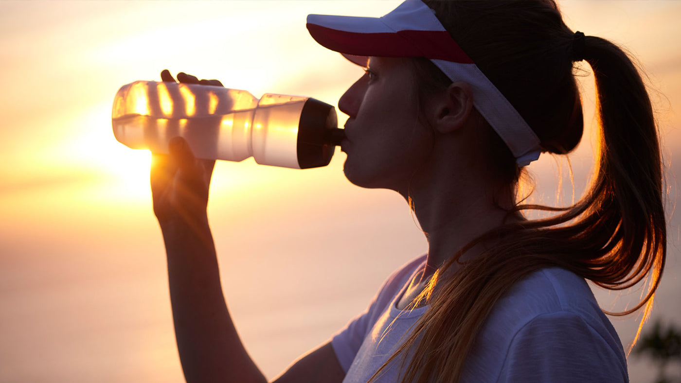 A female runner drinking from a sports water bottle.