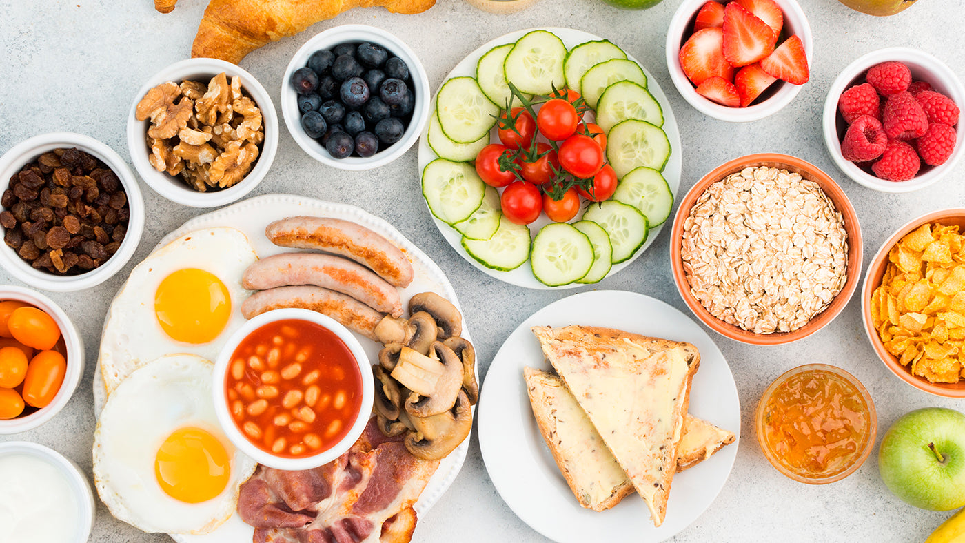 A spread of food with many plates, including an English breakfast, cucumbers, blueberries, toast, grains and more.