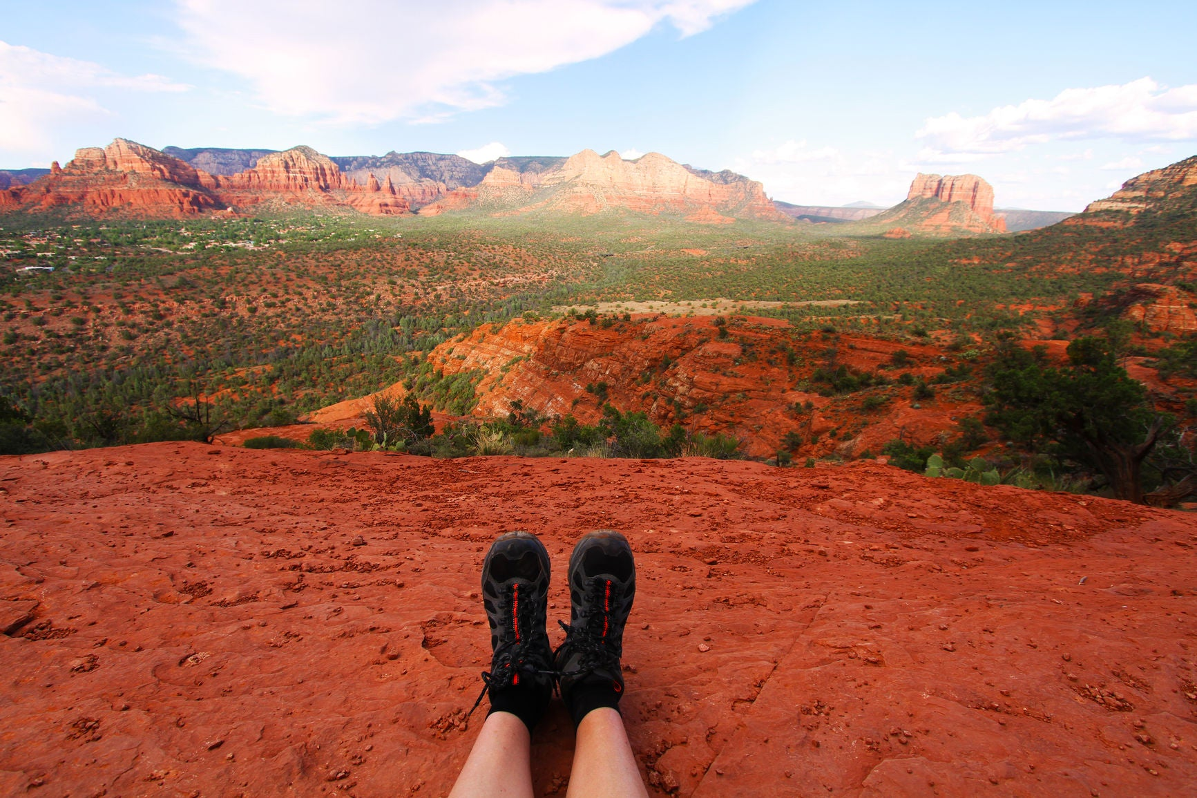 A runner sitting on a plateau overlooking a vista