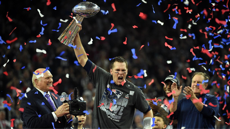 New England Patriots quarterback, Tom Brady, holding the super bowl trophy