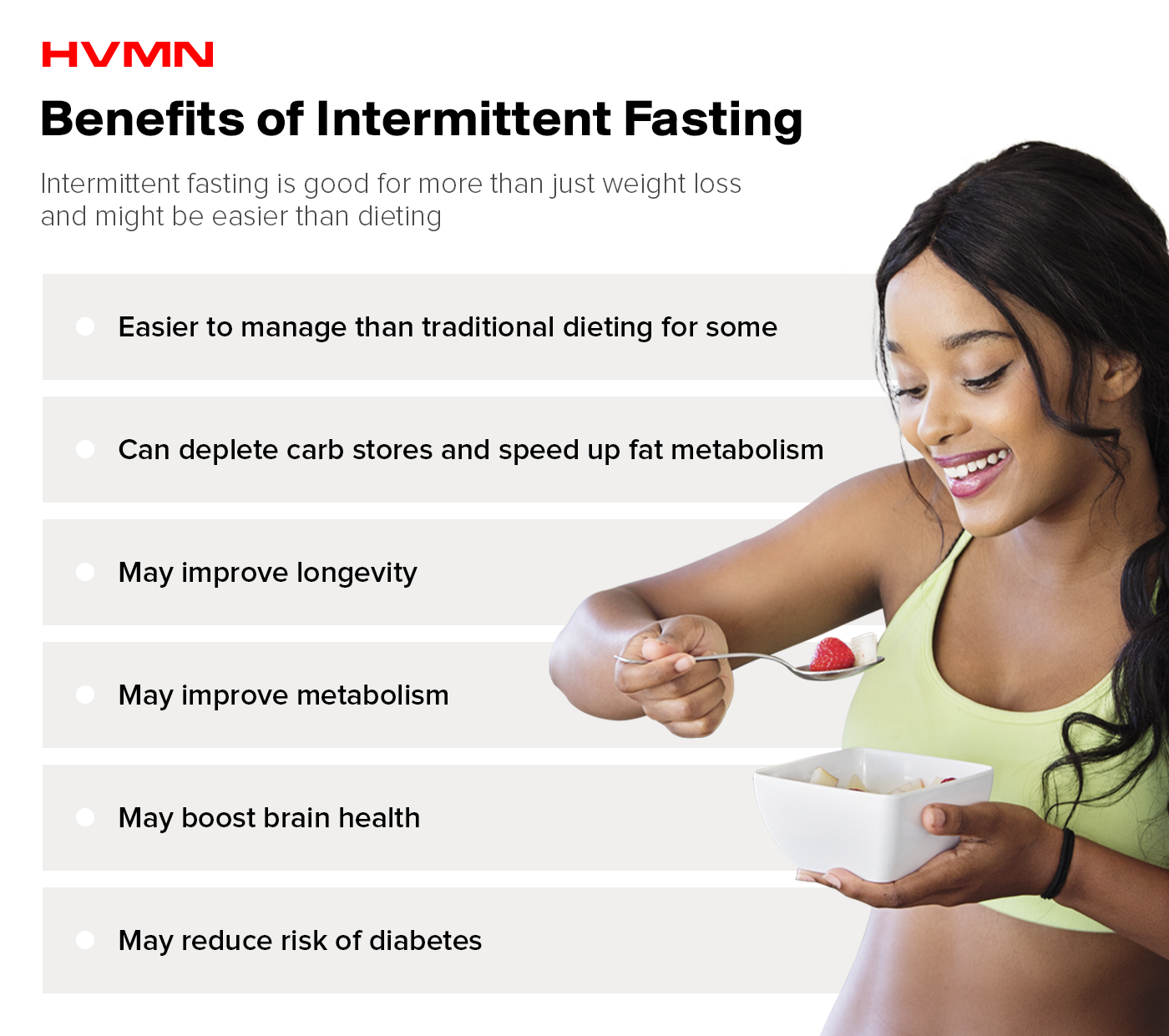 A woman eating a bowl of fruit showing the benefits of intermittent fasting