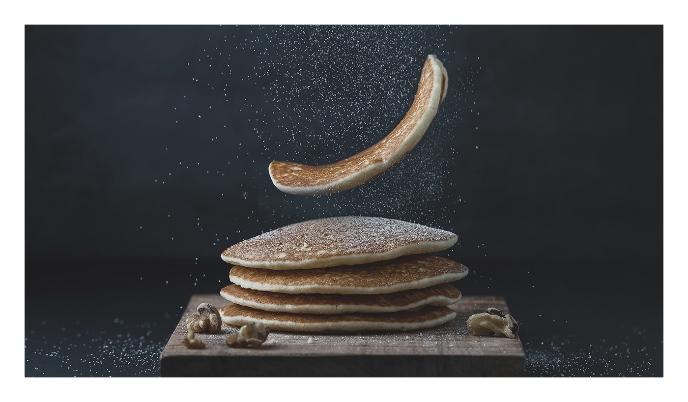 An image of pancakes being plopped down on a wooden cutting board